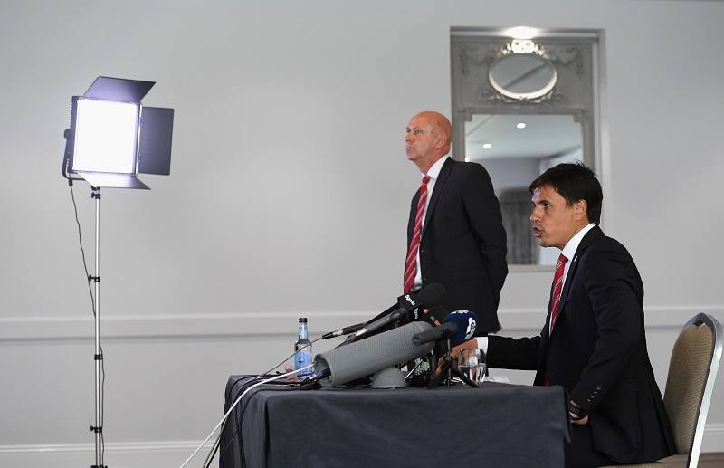 Wales soccer manager Chris Coleman speaks to the media under the watch of his communications manager