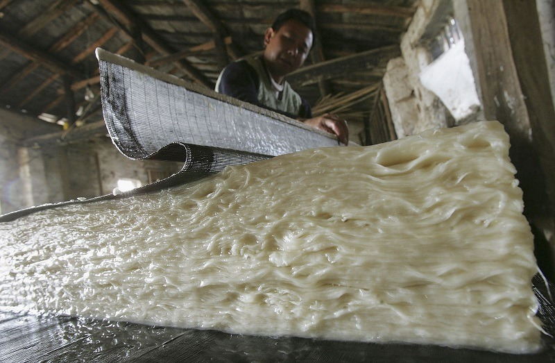 A Chinese worker producing paper from pulp