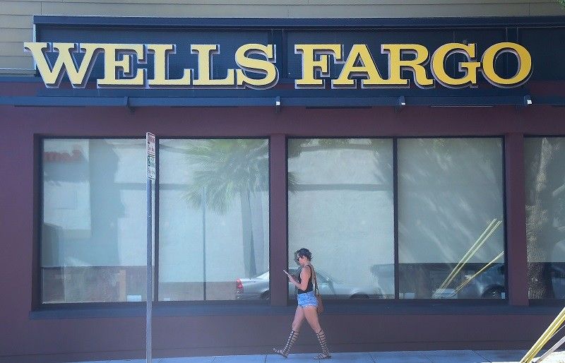 A woman walks past a Wells Fargo branch
