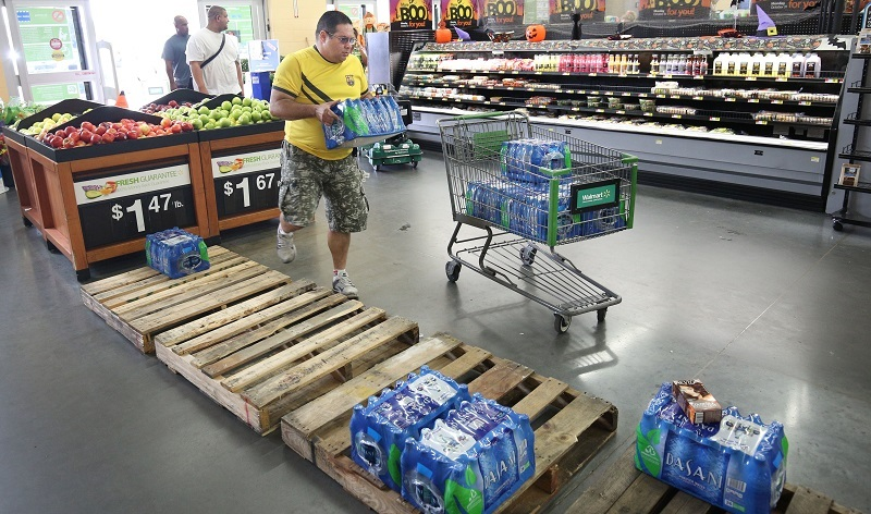 A man empties a few pallets of drinking water at a supermarket