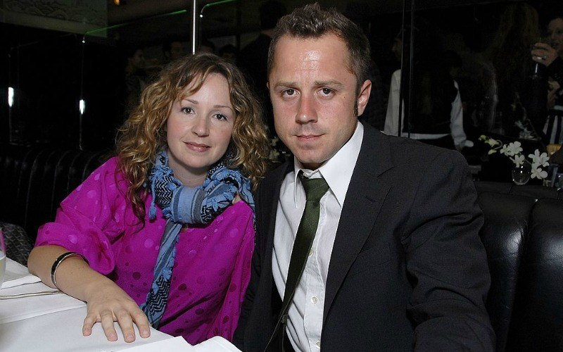 Giovanni and Marissa Ribisi look at the camera as they sit at a table together.