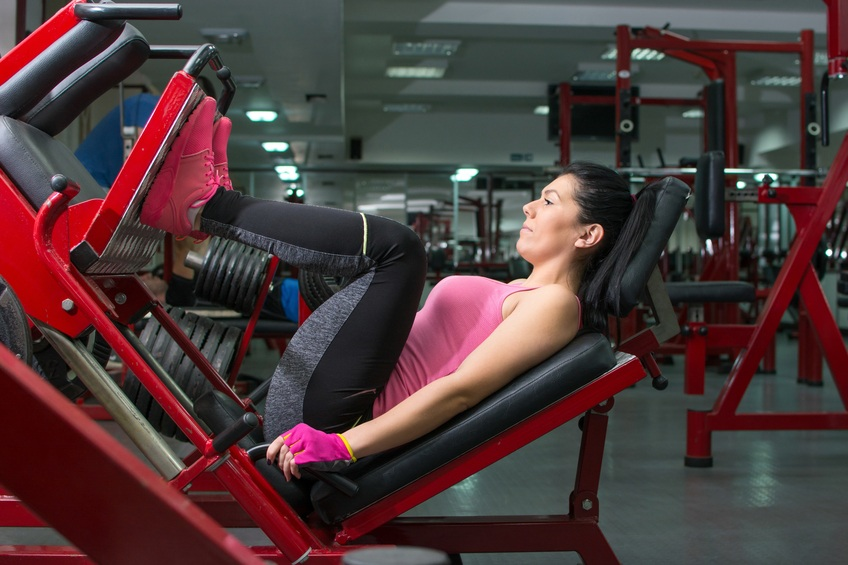 Athletic girl doing the leg press at the gym