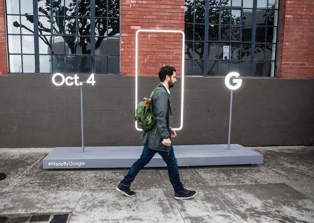 A pedestrian walks by a sign outside an event by Google