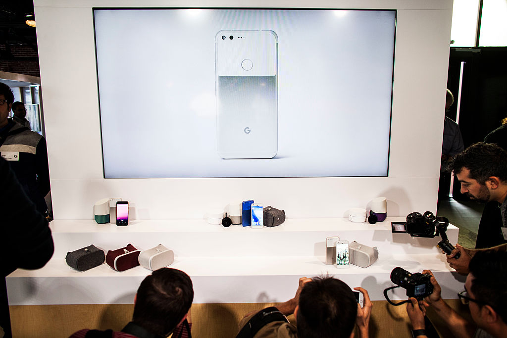 Members of the media photograph a display of Google's Pixel phone