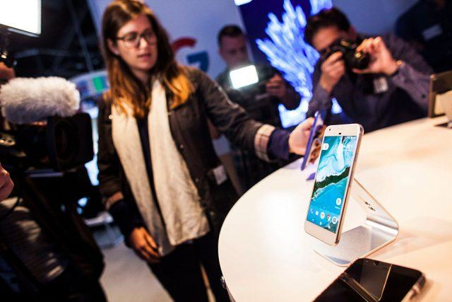 Members of the media examine Google's Pixel phone during an event to introduce Google hardware products