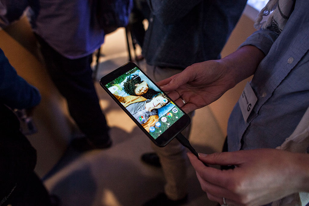 Members of the media examine Google's Pixel phone during an event