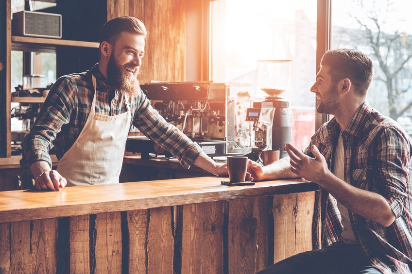 Barista and his customer discussing something with smile