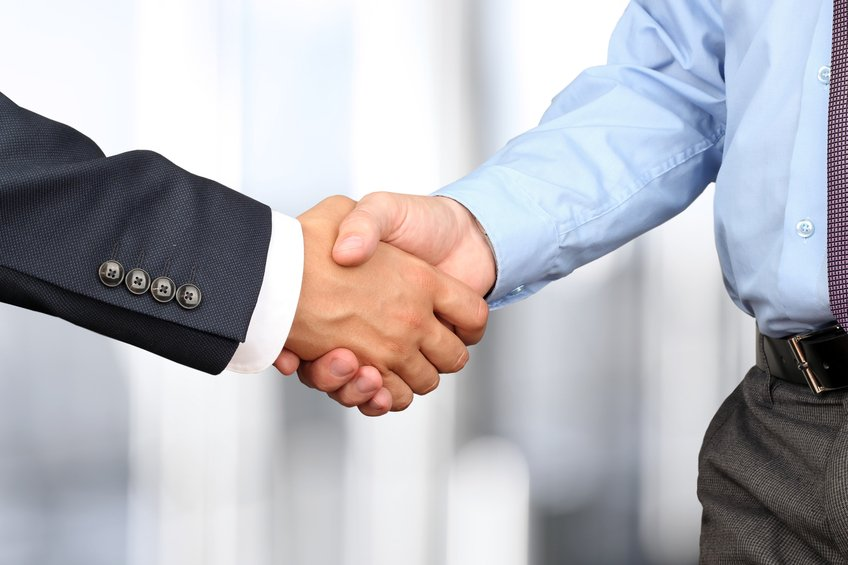 Handshake between two colleagues in office