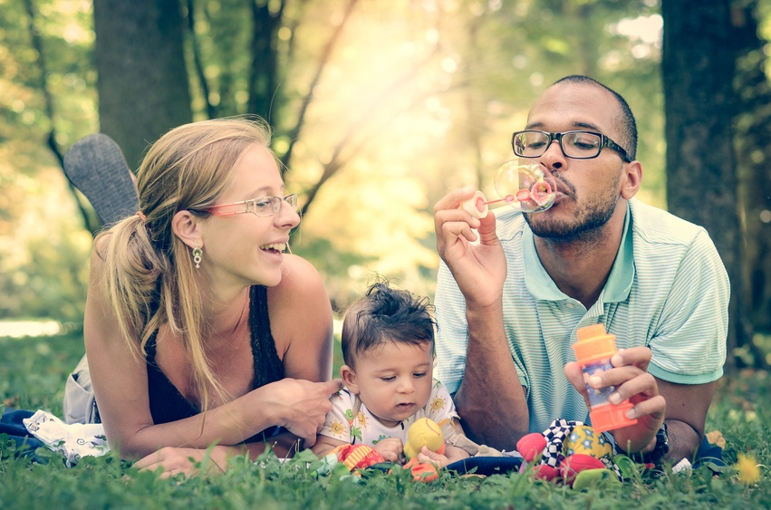 Happy interracial family is blowing bubbles