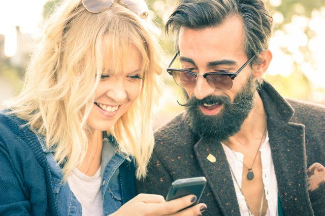 Couple with vintage clothes having fun with smartphone.