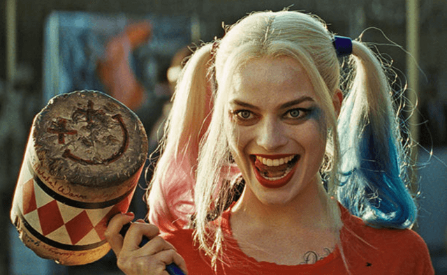 Harley Quinn holding a mallet and smiling while sticking out her tongue.