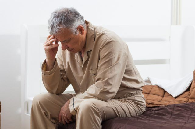 senior man sitting up in bed unable to sleep