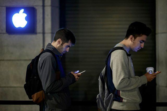 Customers check their mobile phones as they queue at Puerta del Sol Apple Store
