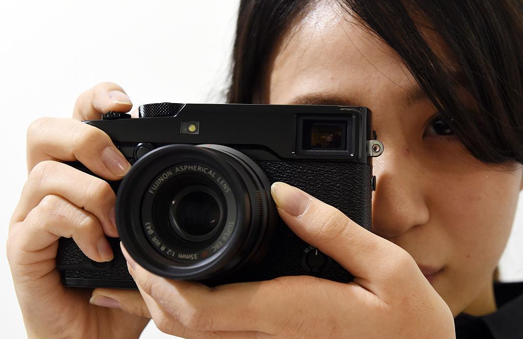 A Fujifilm employee poses with the company's new X-Pro2 premium mirrorless digital camera