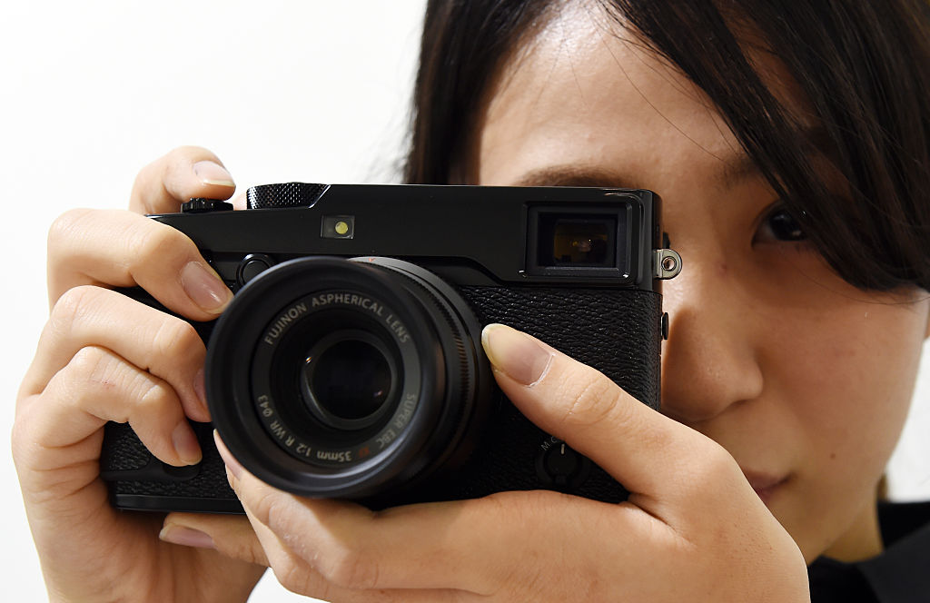 A Fujifilm employee poses with the company's new X-Pro2 premium mirrorless digital camera