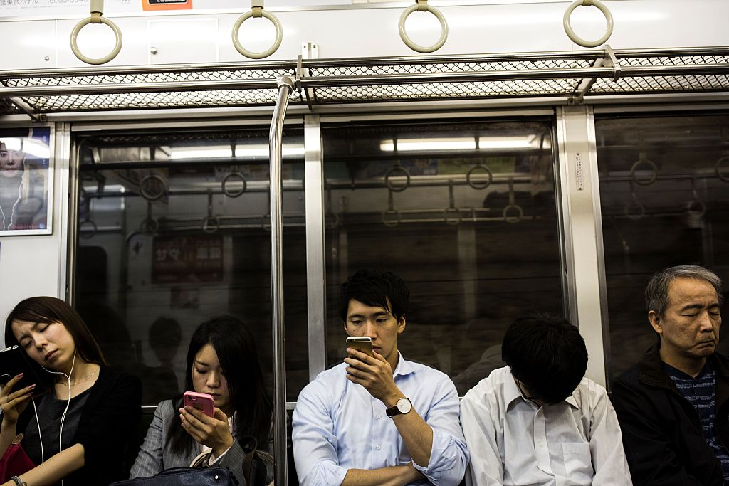 Japanese commuters check their smart phones in a subway