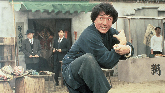 Jackie Chan in a blue jumpsuit, with his fists out, ready to fight