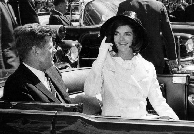 President John F. Kennedy and First Lady Jacqueline Kennedy sitting in a coach.