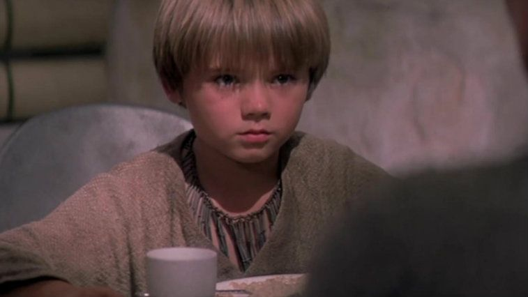 Jake Lloyd in Star Wars: The Phantom Menace, wearing a tan tunic, and looking off into the distance