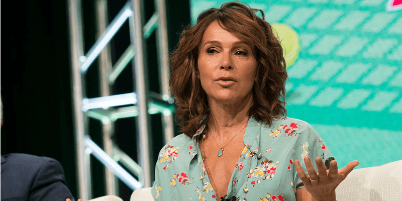 Jennifer Grey sits on stage during a panel while answering interview questions.