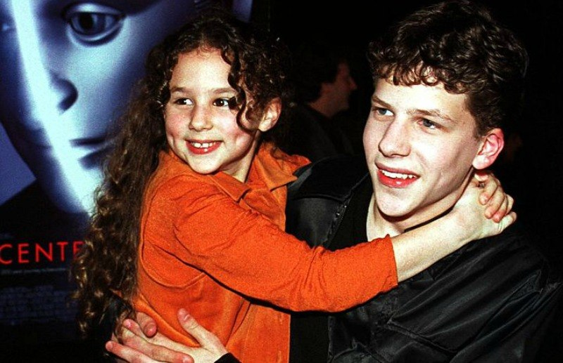 Jesse Eisenberg is holding little Hallie Eisenberg on the red carpet.