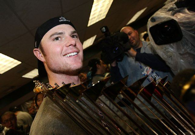 Starting pitcher Jon Lester of the Boston Red Sox celebrates with the trophy in the locker room