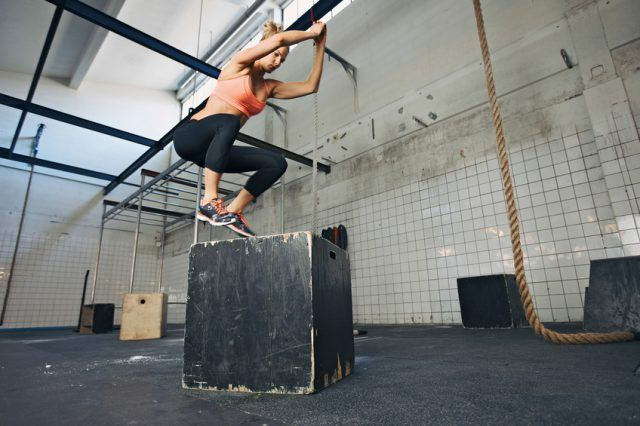 Fit young woman box jumping at a gym