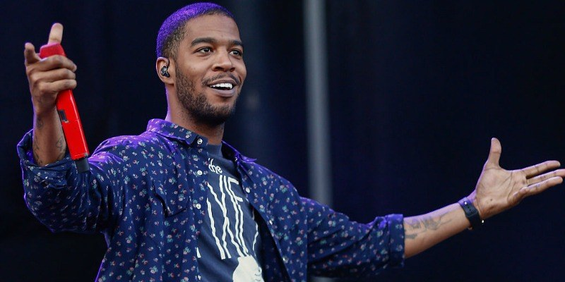 Kid Cudi is smiling and has his arms up on stage.