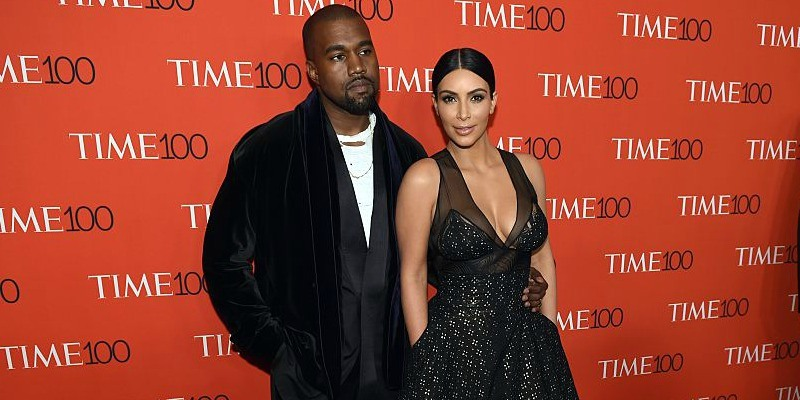 Kim Kardashian and Kanye West pose together in black outfits on the red carpet.