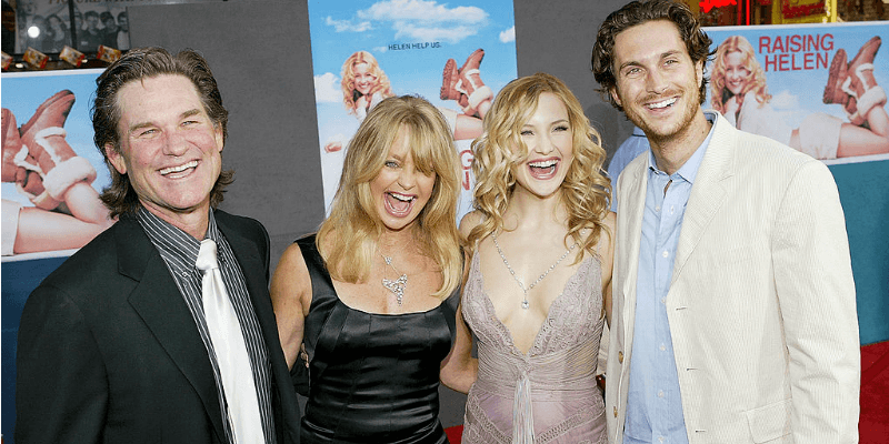 Kurt Russell, Goldie Hawn, Kate and Oliver Hudson pose on the red carpet together smiling.