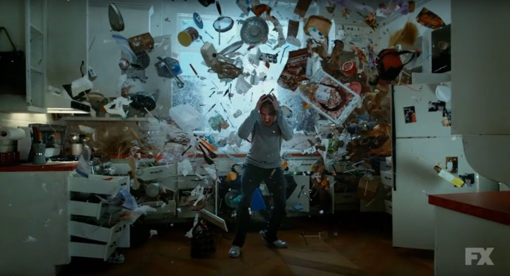 Dan Stevens cowers as objects fly around him in a scene from FX's Legion