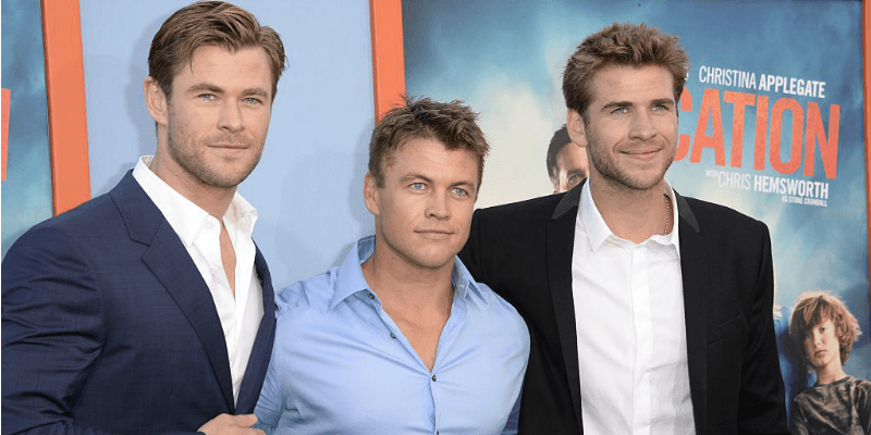 Chris, Luke, and Liam Hemsworth pose together on the red carpet with their arms around each other.