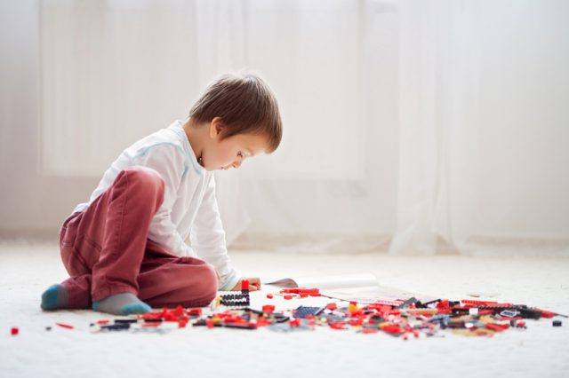 A child plays with blocks on the floor