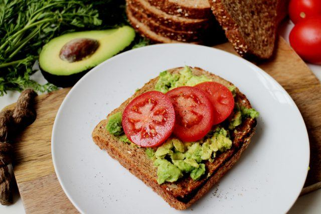 Avocado toast and tomatoes on a white plate.