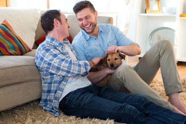 A couple petting a dog in their living room.