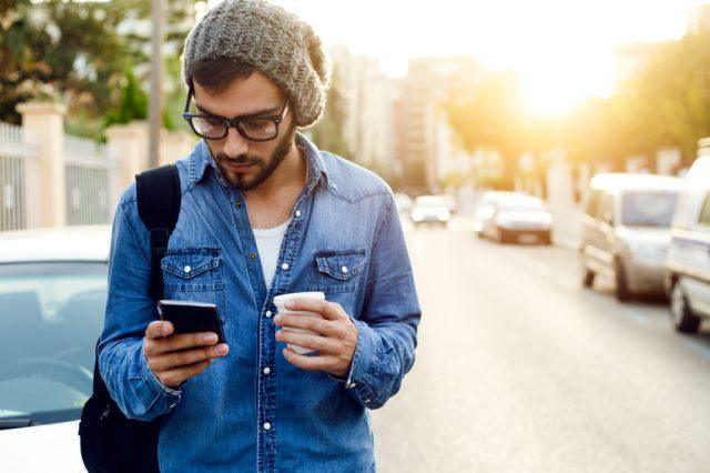 Young man with mobile phone in the street.