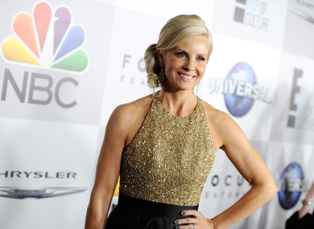 Monica Potter is in a sparkly dress and has her hand on her hip smiling on the red carpet.