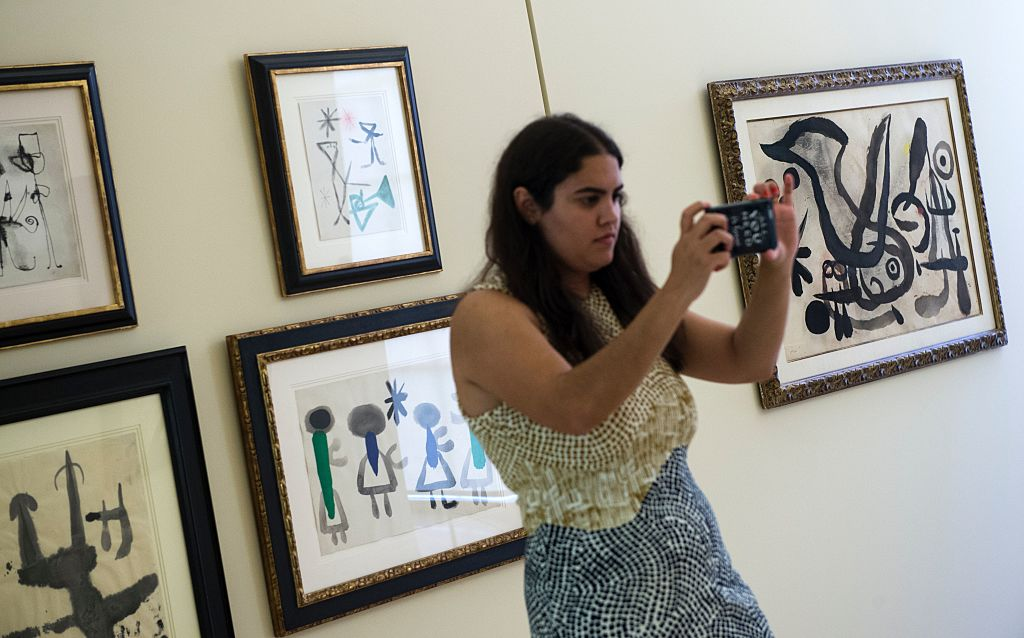 A visitor takes pictures with her smartphone past a piece of the exhibition