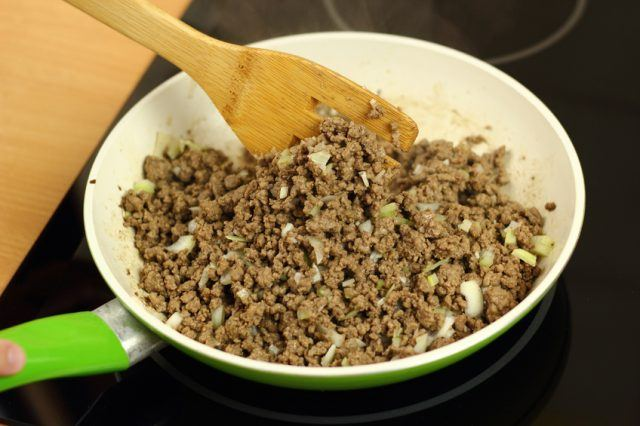 Ground beef and seasonings in a white and green skillet.