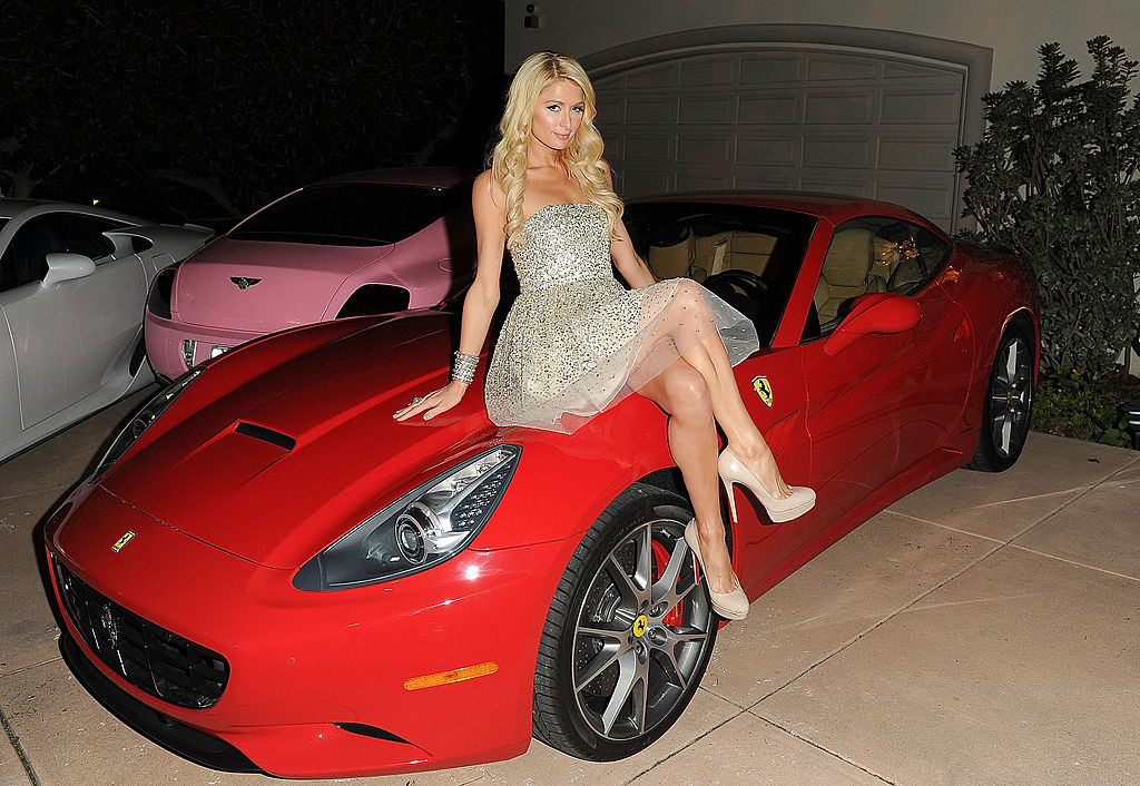 Paris Hilton sits on top of a red car in a silver dress.