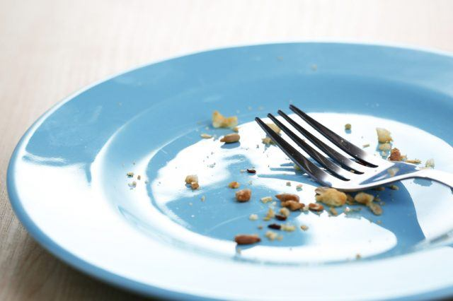 A plate with crumbs and a used fork.
