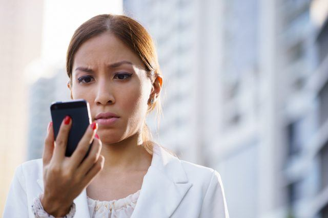 Businesswoman using mobile phone, looking at the emoji Android supports