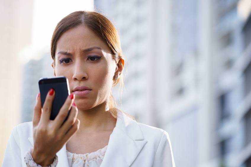 A business woman uses her smartphone outside