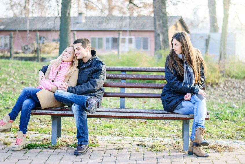A couple of young man and woman teenagers sitting on a bench