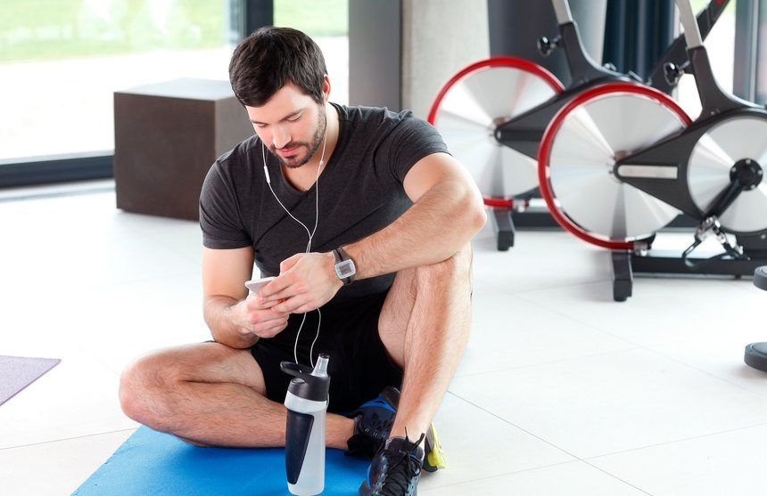 young personal trainer holding in his hand a mobile phone and listening music