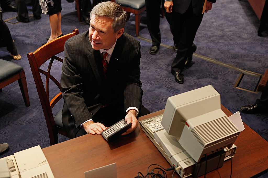 U.S. Sen. Mark Kirk (R-IL) looks at at Tandy hand-held PC-5 and a IBM PC Convertable