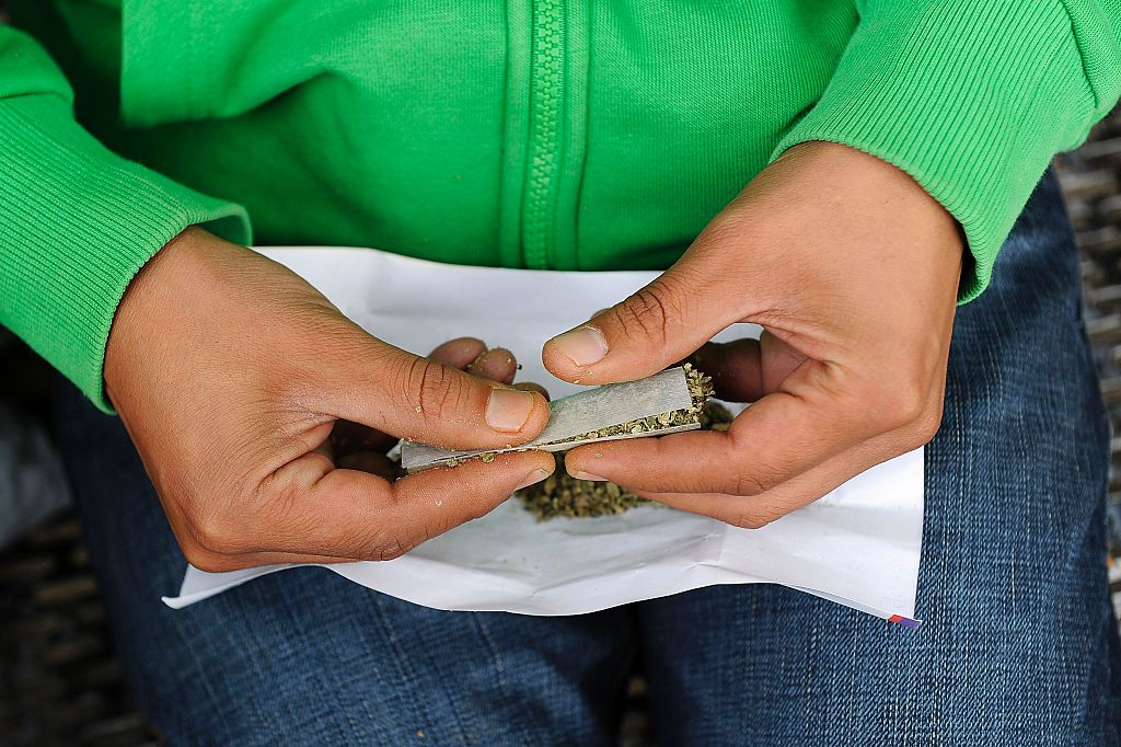Female hands rolling a joint