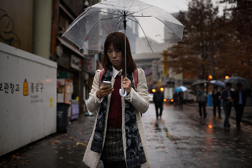 A woman uses a mobile phone as she shelters beneath an umbrella