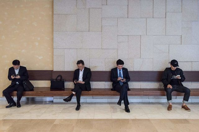 People look at their mobile phones at a mall in the Gangnam district