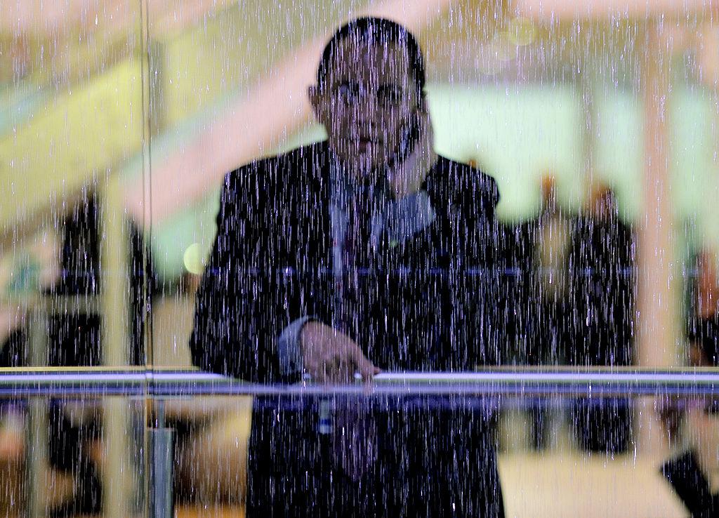 A man speaking on his phone looks through a window pane